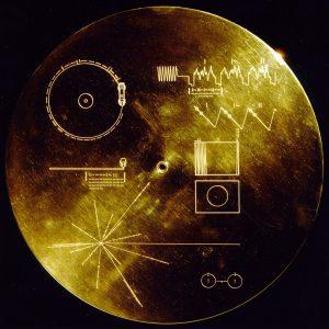 La copertina del disco ricoperto d'oro, del diametro di 12 pollici (30,5 cm.) che si trova all'interno delle sonde Voyager. Le immagini rappresentano con le istruzioni di utilizzo del disco, qualora siano ricevute da un'entità intelligente. Il disco all'interno riproduce saluti in 60 lingue, musiche etniche e vari suoni. NASA/JPL, Pubblico Dominio