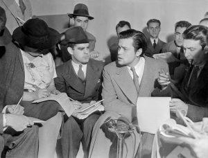Orson Welles durante la conferenza organizzata per convincere i media che lo scopo della trasmissione sulla Guerra dei Mondi non era il causare il panico (credit: Acme News Photos, Pubblico Dominio)