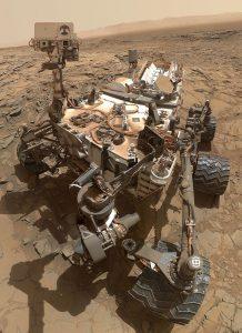 """Un """"selfie"""" di Curiosity (in realtà una fotocomposizione di molte immagini scattate il 6 ottobre 2015) scambiata da alcuni teorici del complotto per un falso, poiché sembra che l'autore della foto sia esterno al rover (credit: NASA, Pubblico Dominio)"""