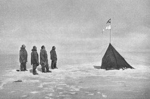La spedizione di Roald Amundsen osserva la bandiera norvegiese appena piantata sul Polo Sud (credit: Pubblico Dominio)